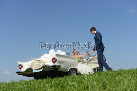 groom helping bride out of car