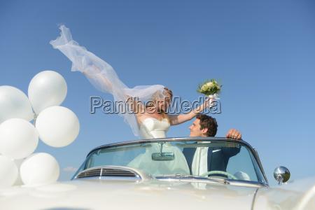bride and groom in open top