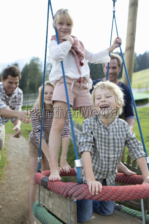 father pushing children on swing in