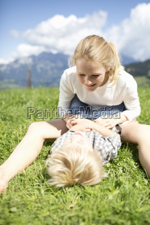 teenage girl playing with younger brother