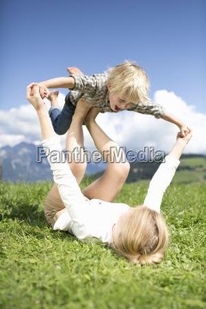 boy balancing on teenage sisters feet