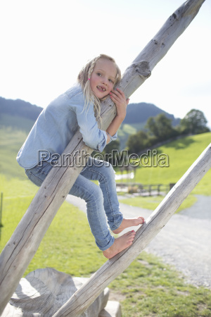 young girl playing on dead tree
