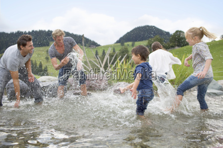 fathers with children having water fight