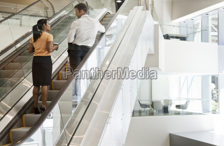 businessman and woman on escalators and