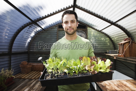 hispanic man with new plants for
