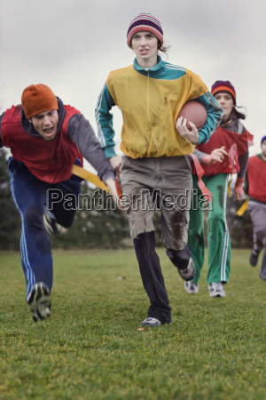 caucasian woman running with the football
