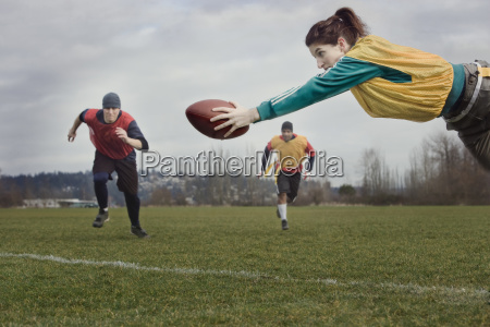 caucasian woman diving with a football