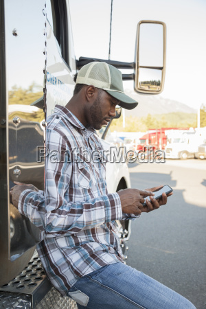 black man truck driver texting while