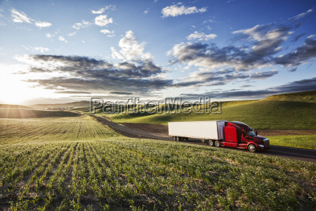 commercial truck driving through farmlands in