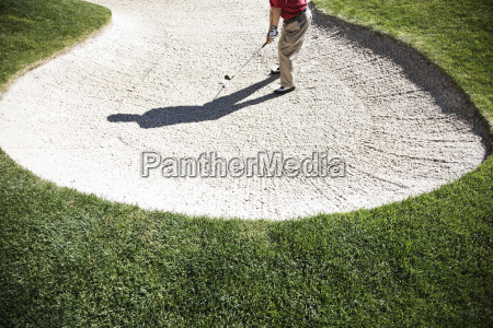 senior golfer playing out of a