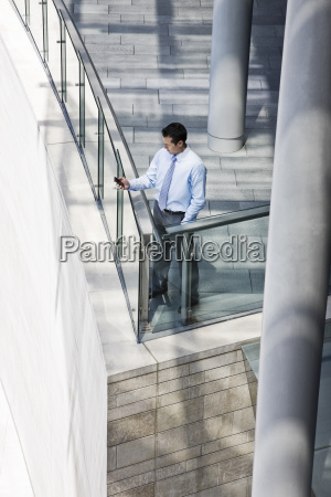 caucasian businessman texting from a balcony