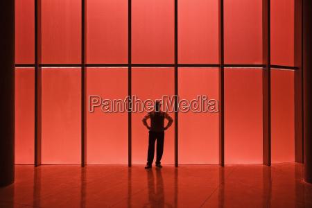 geschaeftsmann steht neben rot getoenten fenstern