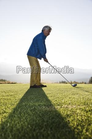 an asian senior man teeing up