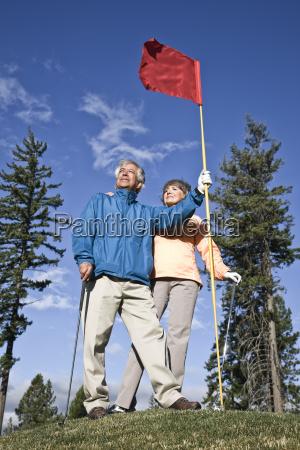 senior golfing couple on a green