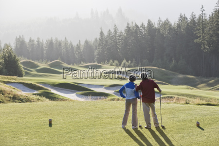 senior golfing couple surveying the next