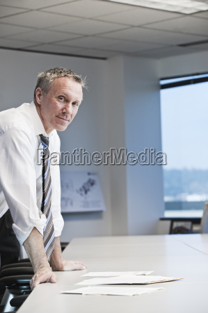 caucasian businessman looking over paperwork at