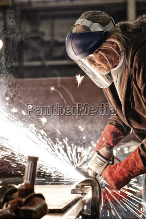 factory worker grinding a steel edge