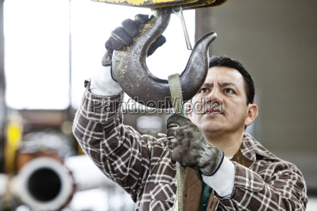 hispanic man factory worker attaching a