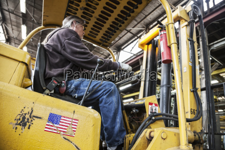 caucasian man factory worker driving a