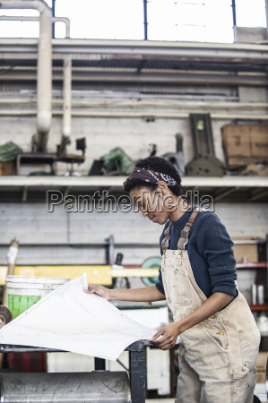 black woman factory worker going over