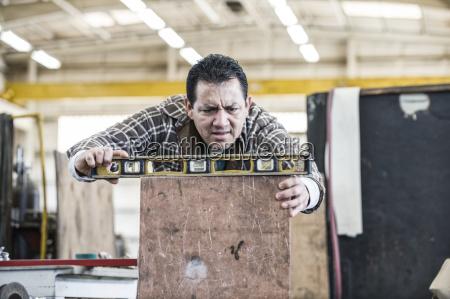 hispanic man factory worker using a