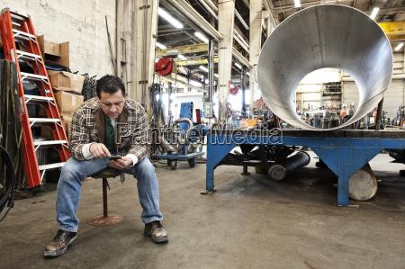 hispanic man factory worker checking a