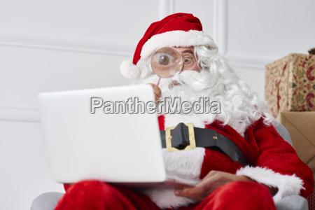 santa claus mit laptop mit lupe