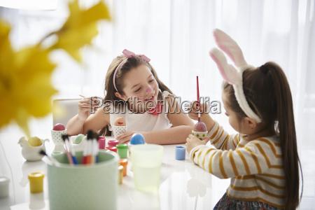 schwestern sitzen am tisch und malen