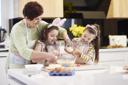 grandmother and granddaughters baking easter cookies
