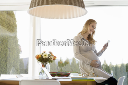 smiling pregnant woman sitting on desk