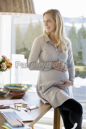 smiling pregnant woman working at home