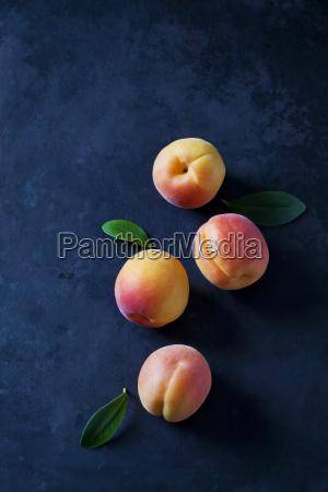 vier aprikosen auf dunklem grund