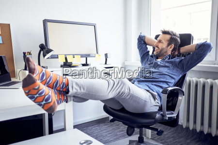relaxed man sitting at desk in