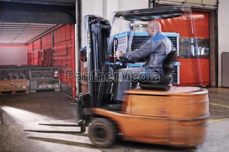 gabelstaplerfahrer der lastwagen laedt