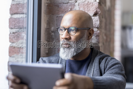 portrait of pensive man with tablet