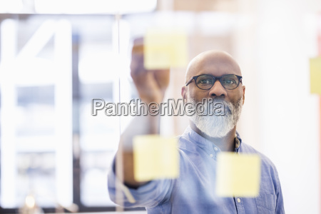 portrait of businessman taking adhesive note