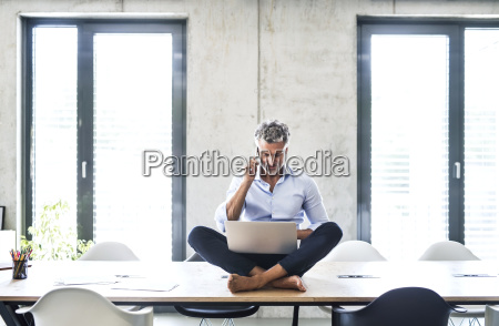 mature businessman sitting barefoot on desk