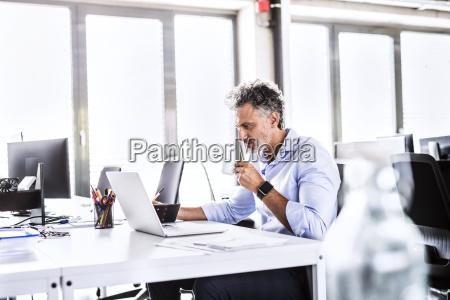 mature businessman sitting at desk in