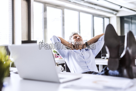 relaxed mature businessman sitting at desk