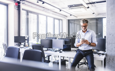smiling mature businessman sitting on desk