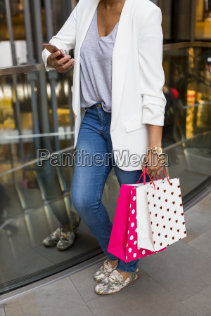 woman using cell phone in shopping