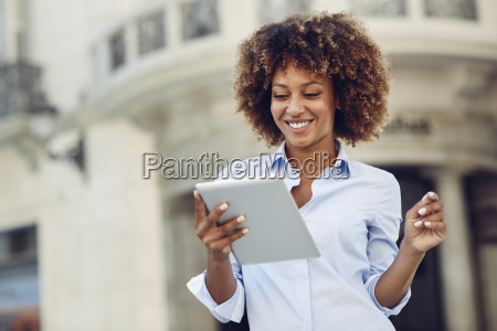 smiling woman with afro hairstyle using