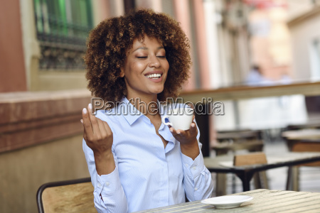 smiling woman with afro hairstyle sitting