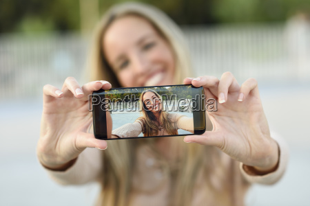 happy young woman taking selfie with