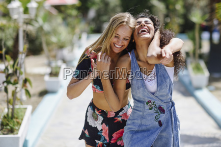 two laughing young women outdoors in