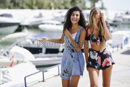 two laughing young women at waterfront