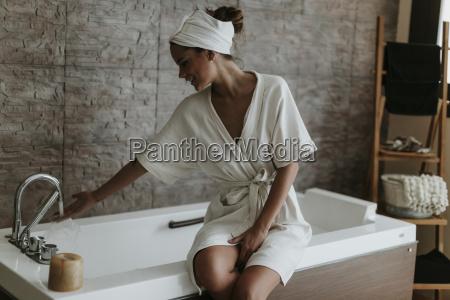 young woman preparing a bath in
