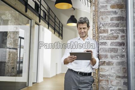 portrait of mature businessman using tablet
