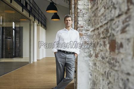 portrait of confident businessman leaning against