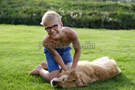 happy teenage boy playing with dog